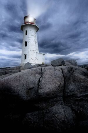 The lighthouse at Peggys Cove in Nova Scotia Canada at dusk as a storm grows.