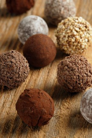 An assortment of chocolate truffles on old wood table.  Very Shallow depth of field, focusing on middle truffle. Stock Photo - 5346359