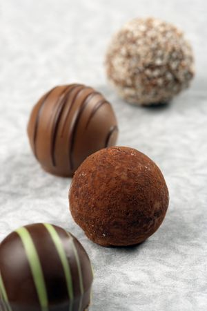 A small assortment of chocolate truffles and pralines on paper. Very Shallow depth of field, focusing on middle truffle.