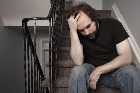 woe: Depressed adult male sitting on stairs. De-saturated slightly for even sadder look.