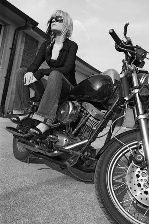 Black and white image of a beautiful blonde female sitting on a motorcycle.