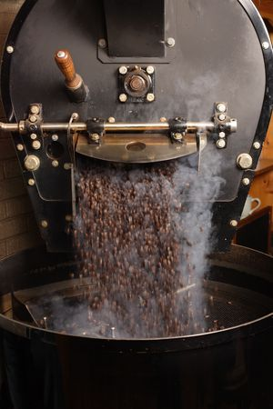 roaster: The freshly roasted coffee beans from a large coffee roaster being poured into the cooling cylinder.  Motion blur on the beans.