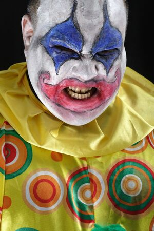A nasty evil clown, angry and looking mean. Harsh lighting from below, focus on the teeth. photo
