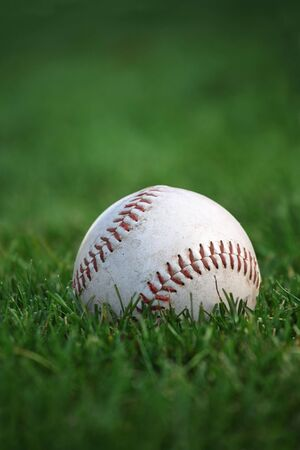 An old well-used baseball sitting in the grass of the outfield. Plenty of space for text. Selective focus on red stitches. photo