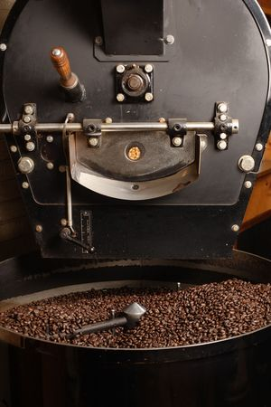 roaster: The freshly roasted coffee beans from a large old coffee roaster being stirred in the cooling cylinder. Stock Photo