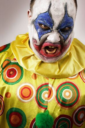 A nasty evil clown, angry and looking mean. Harsh lighting, focus on the teeth. photo