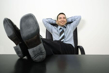 feet on desk: happy businessman reclining with his feet up and hands behind his head.