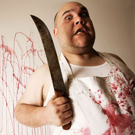 harsh: Crazy insane butcher covered with blood.  Harsh lighting from below for more disturbing feel. Stock Photo