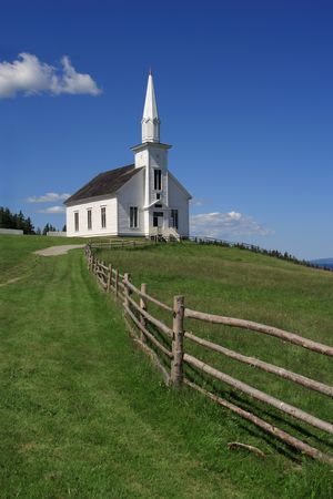 Photo of a little white wooden church in the countryside. photo