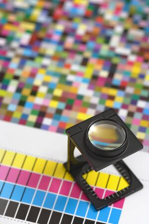 prepress: Shallow depth of field image of a printers loupe on printed sheet.  Focus is on the top of the loupe. Stock Photo