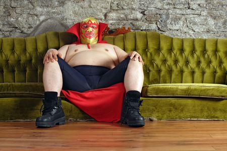 Photograph of a Mexican wrestler or Luchador sitting on a green couch waiting for his match to begin. photo