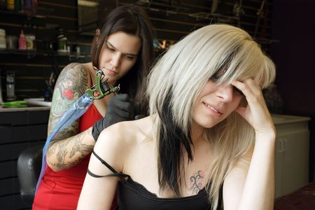 A female tattoo artist applying her craft onto the back and arm of a female in her 30's. (Property release for tattoo artwork attached) Stock Photo - 7289357