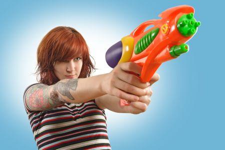 pointing gun: a beautiful redhead about to shoot a water gun. Stock Photo