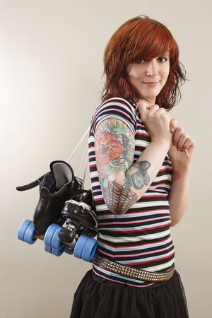 Photograph of a roller derby girl holding her skates by the laces. photo