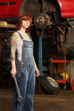 young beautiful redhead mechanic wearing overalls and holding a huge wrench.  Attached property release is for arm tattoos.  photo