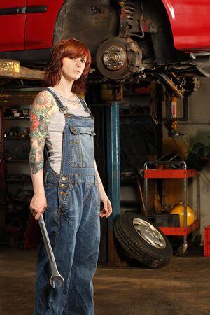 고치다: young beautiful redhead mechanic wearing overalls and holding a huge wrench.  Attached property release is for arm tattoos.