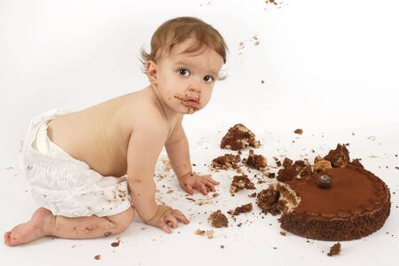 An adorable one year old girl enjoying her first birthday cake.  photo