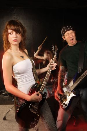 Band playing on a stage. Female guitarist, male bassist and female drummer. Shot with strobes and slow shutter speed to create lighting atmosphere and blur effects. Slight motion blur on performers. Stock Photo - 7336646