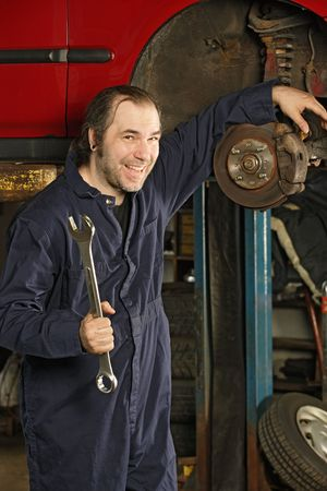 A crazy happy mechanic fixing brakes. Stock Photo - 7356728