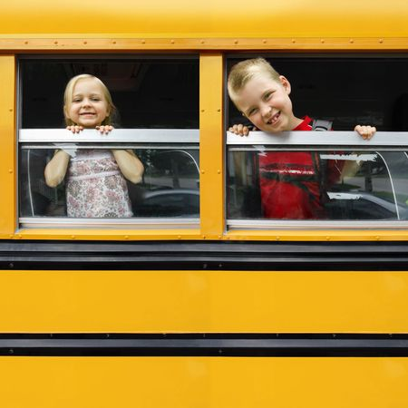 school buses: two happy children looking out the windows of a yellow school bus. Plenty of space for text.