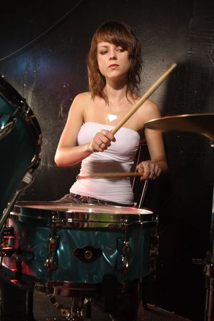 Photograph of a female drummer playing a drum set on stage. photo