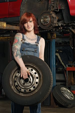 car hoist: Photo of a young beautiful redhead mechanic wearing overalls and holding a wheel.  Attached property release is for arm tattoos. Stock Photo