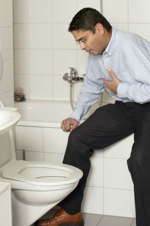 Photo of an adult male in his late thirties with stomach sickness about to vomit into his toilet. photo