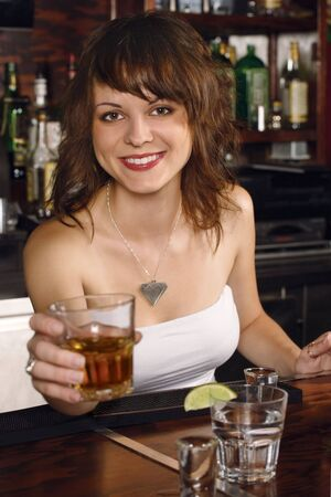 Photo of a beautiful bartender serving you a glass of whisky. Stock Photo - 7502387