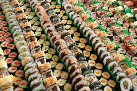 Photo of fresh maki sushi platter with a lot of variety. Selective focus on middle of the platter.