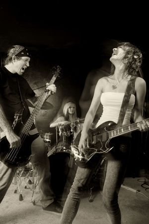 Band playing on a stage. Male bassist with female guitarist and drummer. Shot with strobes and slow shutter speed to create lighting atmosphere and blur effects. Slight motion blur on performers. Stock Photo - 7573587