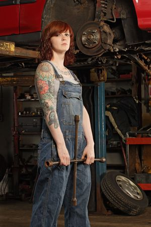 Photo of a young beautiful redhead mechanic wearing overalls and holding a huge wrench.  Attached property release is for arm tattoos. Stock Photo - 7602370