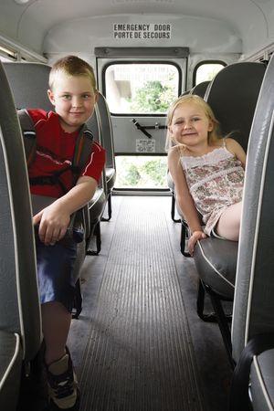 enfant banc: Photo de deux enfants heureux, assis dans un autobus scolaire.