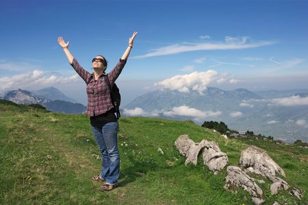 Photo of an active female with backpack and hands pointing to the sky while hiking up a mountain trail.