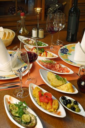 A table setting full of traditional Spanish tapas and wine. Stock Photo