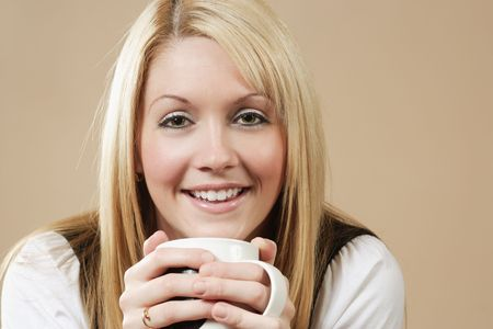 Photo of a smiling female holding a coffee, hot chocolate, or tea. photo
