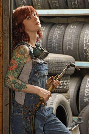 overalls: Foto de un mec�nico de joven pelirroja hermoso vistiendo overol y sosteniendo una antorcha de soldadura. Versi�n de la propiedad adjunta es para tatuajes de brazo.