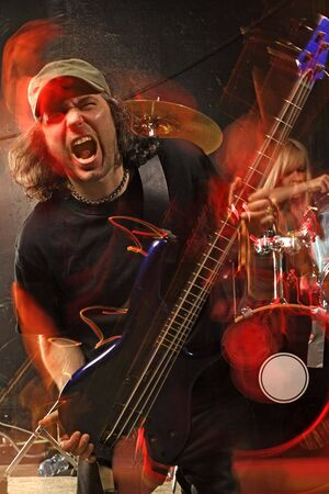 Bass guitarist playing on a stage. Shot with strobes and slow shutter speed to create lighting atmosphere and blur effects. Intense motion blur on performers. Stock Photo - 8260815