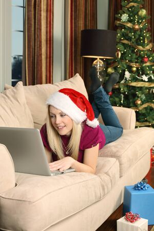 Photo of a beautiful blond female sitting on a couch using a laptop to shop for Christmas gifts. photo