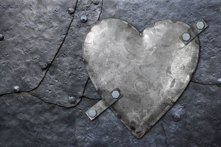 Photo of a galvanized metal heart bolted to old hammered metal plates with rivets. photo