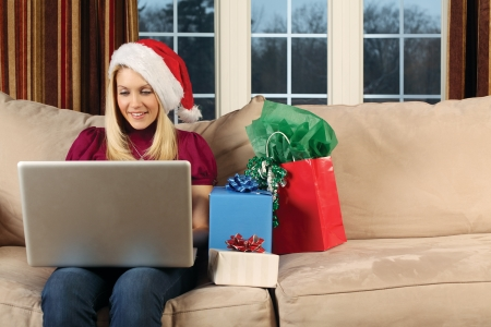 beautiful blond female sitting on a couch using a laptop to shop for Christmas gifts. Stock Photo - 8721337