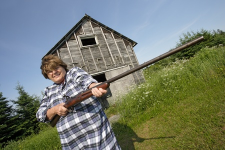 Photo of an older woman holding a large rifle. photo