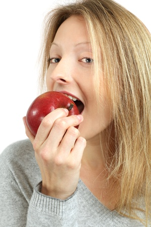 Photo of a beautiful blond woman biting into a red juicy apple. Stock Photo - 8821969