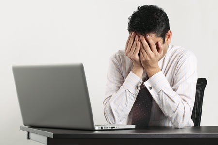 tired businessman: an Indian male frustrated with work sitting in front of a laptop. Stock Photo
