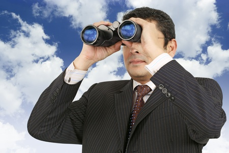 late thirties: An Indian businessman in his late thirties looking through binoculars with a cloudy blue sky in the background.