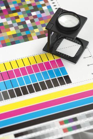 imprenta: Profundidad superficial de imagen de campo de una lupa de impresoras en hoja impresa.  Foco est� en la parte inferior de la lupa. Foto de archivo