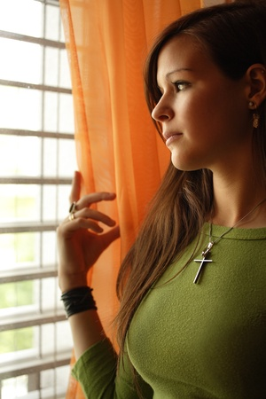 thinking woman: Photo of a beautiful young female looking out a window.  Could be a religious theme, or contemplation theme.