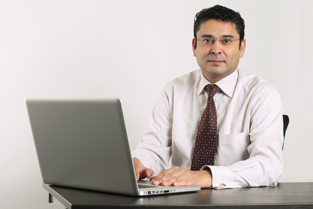 Indian male happy at work sitting in front of a laptop. photo
