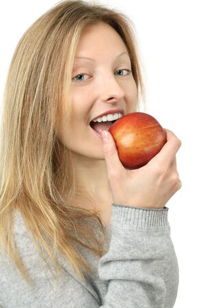 Photo of a beautiful blond woman holding a red juicy apple and about to take a bite. Stock Photo - 9124739