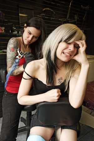A female tattoo artist applying her craft onto the back and arm of a female in her 30's. (Property release for tattoo artwork attached) photo