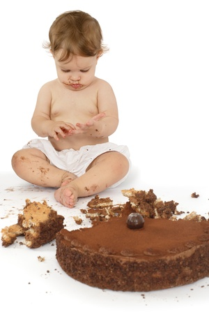 mess: An adorable one year old girl enjoying her first birthday cake.